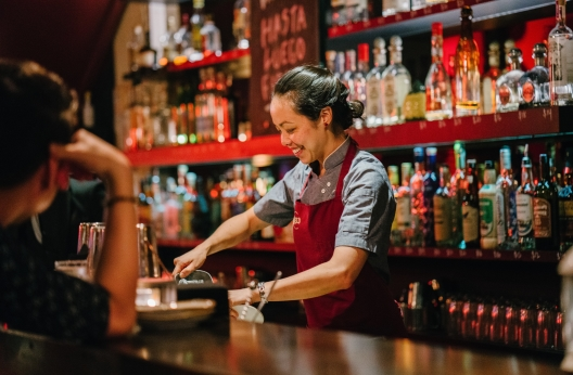 woman bartender smiling while mixing liqueurs 1301547 v2